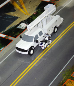 Image of scale model exhibit with scale vehicles located at the collision area.